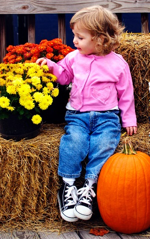 Little girl with fall flowers, haybale and pumpkin